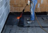 picture of membrane  - Worker preparing part of bitumen roofing felt roll for melting by gas heater torch flame - JPG