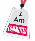 stock photo of tasks  - I Am Committed words on an employee name badge or ID card or tag to illustrate dedication to the job and determination to complete a task or work - JPG