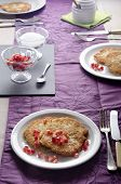 stock photo of home-made bread  - laid table with rustic home made potato pancakes sugar in a bowl on slate fresh pomegranate seed lilac table runner fork knife tea spoon and honey pot - JPG