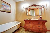 stock photo of tub  - Bathroom with claw foot tub carved wood vanity cabinet and mirror - JPG