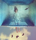 image of sky diving  -  a woman in a dress made of book pages in a box under water with the sky beneath her  - JPG