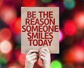 picture of mantra  - Be The Reason Someone Smiles Today card written on colorful background with defocused lights - JPG