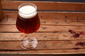 stock photo of crate  - Glass of amber beer standing in an old dirty wooden crate - JPG