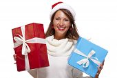 stock photo of vivacious  - Vivacious attractive young woman in a red Santa hat celebrating Christmas holding up colorful red and blue gift boxes with a joyful smile on white - JPG