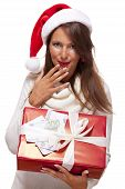 stock photo of vivacious  - Vivacious beautiful young woman wearing a Santa hat with a large red Christmas gift and money conceptual of successful Xmas shopping and payment on white - JPG