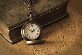 stock photo of time study  - An antique pocketwatch and book come together to remember the wisdom of the old days - JPG