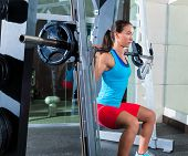 image of squatting  - girl squats in multipower squatting smith machine barbell at gym smith - JPG