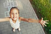 stock photo of hopscotch  - cheerful little girl playing hopscotch on playground outside - JPG