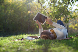 picture of grass  - woman lying on bedding on green grass with ipad during picknic in the park - JPG