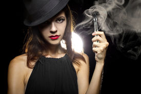 image of tobacco smoke  - woman smoking or vaping an electronic cigarette to quit tobacco - JPG