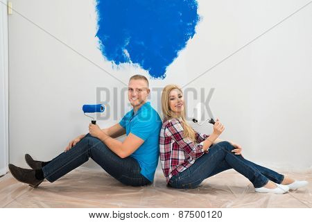Couple Sitting On The Floor Near The Painted Wall