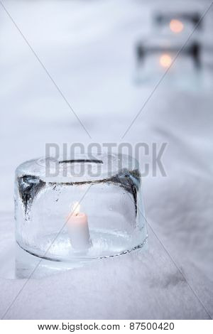 Ice lantern with white candle burning inside