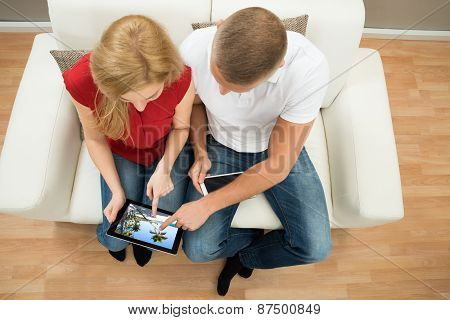 Couple On Sofa Watching Video On Digital Tablet
