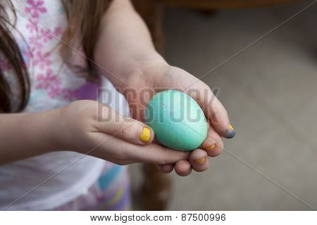 Girl With Yellow Nails Holding Blue Easter Egg