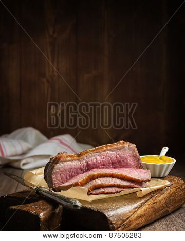 Roast topside of beef sliced on rustic board with pot of mustard