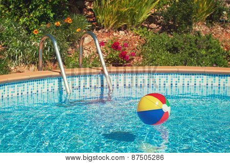 Beach ball floating in summer swimming pool with vintage feel