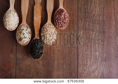 Different kinds of rice in spoons on wooden background