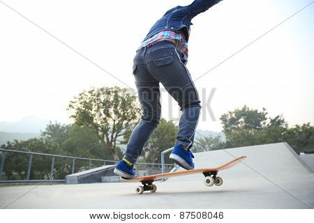 skateboarder jumping on skateboard at skate park