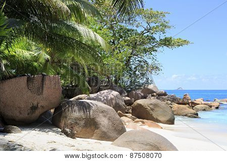 Large granite boulders in Indian Ocean on the beach of Anse Lazio.