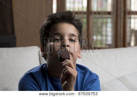 Child enjoying ice cream covered with chocolate at home