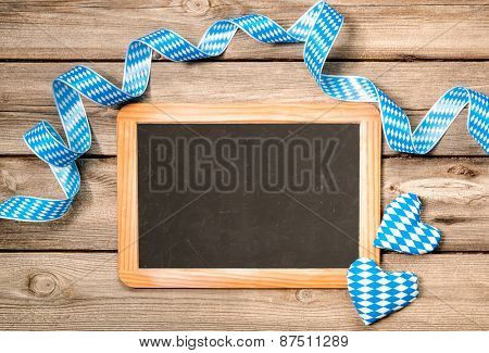 Background with empty board, Bavarian ribbon and hearts, Oktoberfest