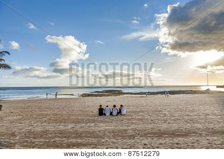 Young People Wearing Bro Tanks Sit At The Beach