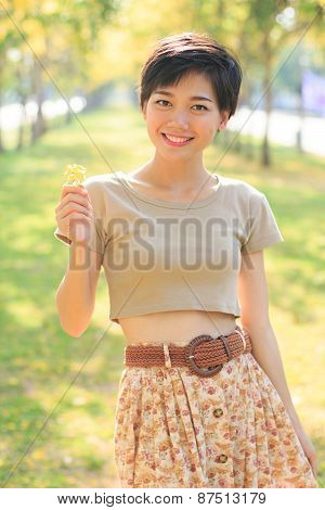 Portrait Of Young And Beautiful Asian Woman Standing In Park With Little Flowers In Hand Smiling To