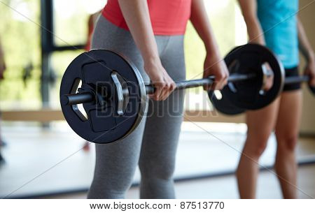 fitness, sport, training, people and lifestyle concept - group of women with barbells flexing muscles in gym