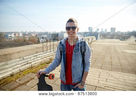 sport, leisure, people and teenage concept - smiling young man or teenager with longboard on city street