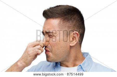 emotions, gesture and people concept - man wrying of unpleasant smell and closing his nose