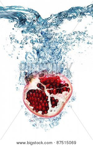 Fresh Pomegranate dropped into water with splash isolated on white
