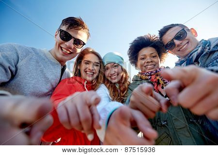 people, leisure, gesture and teenage concept - group of happy teenage friends pointing fingers on city street