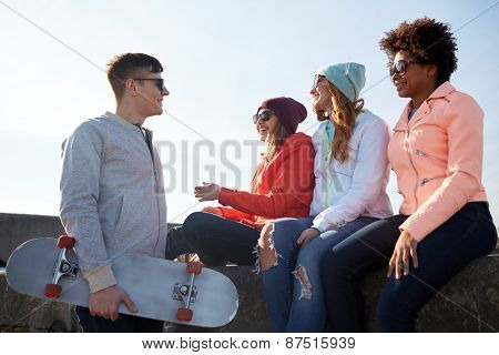 people, leisure and sport concept - group of happy teenage friends with longboard talking on city street