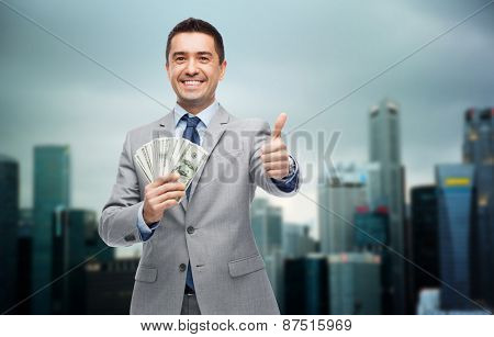 business, people and finances concept - smiling businessman with dollar money showing thumbs up over city background