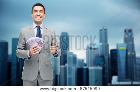 business, people and finances concept - smiling businessman with european money showing thumbs up over city background
