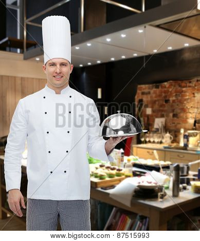 cooking, profession and people concept - happy male chef cook holding cloche over restaurant kitchen