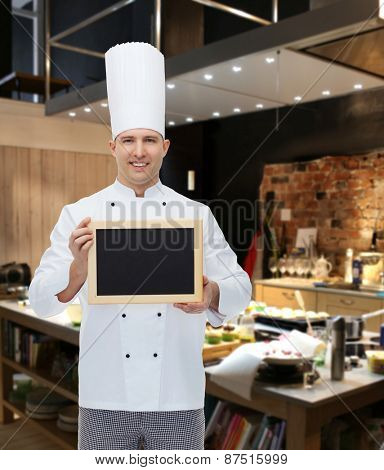 cooking, profession, advertisement and people concept - happy male chef cook showing and holding blank menu board over restaurant kitchen