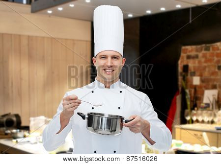 cooking, profession and people concept - happy male chef cook with pot and spoon over restaurant kitchen