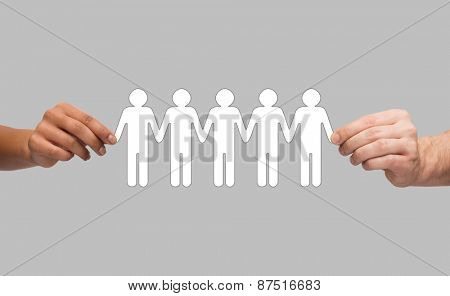 community, unity and teamwork concept - multiracial couple hands holding paper chain people over grey background