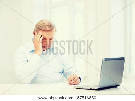 business, tax, office, school and education concept - old man filling a form at home