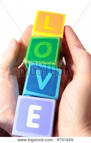 Love In Wooden Play Blocks Letters Held In Hands