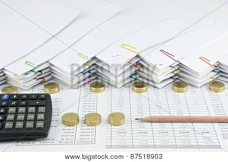 Brown Pencil With Black Calculator Between Pile Of Gold Coins
