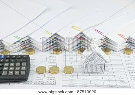 House With Calculator Between Pile Of Gold Coins