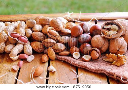 Tasty Nuts On A Wooden Table In Field