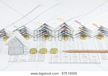 House With Brown Pencil Between Pile Of Gold Coins