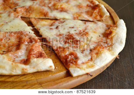 Whole pizza margherita on wooden plate