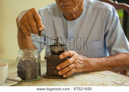Asian Senior Man With Vintage Coffee Grinder