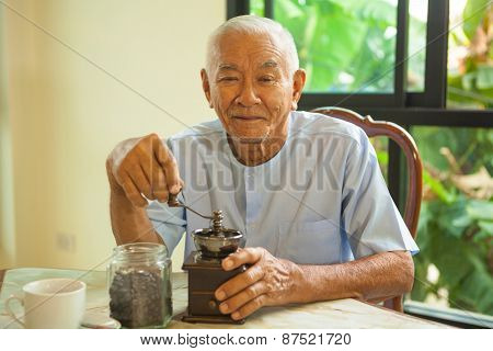 Asian Senior Man With Vintage Coffee Grinder