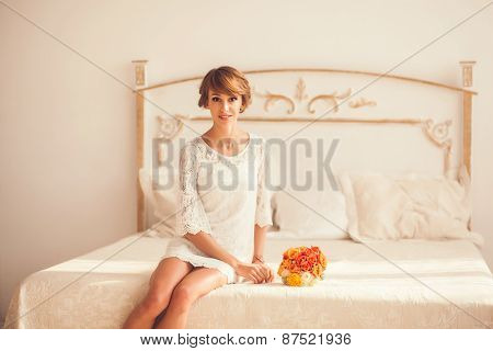 Pretty Model Sitting On The Bed In The Bedroom