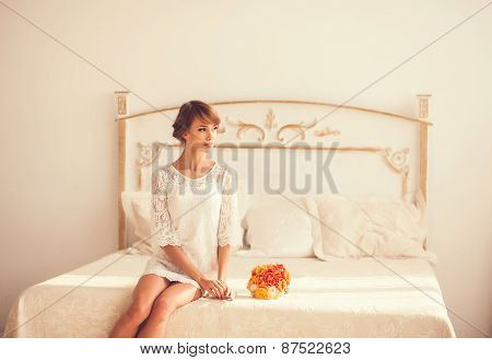 Beautiful Girl Sitting On A Bed